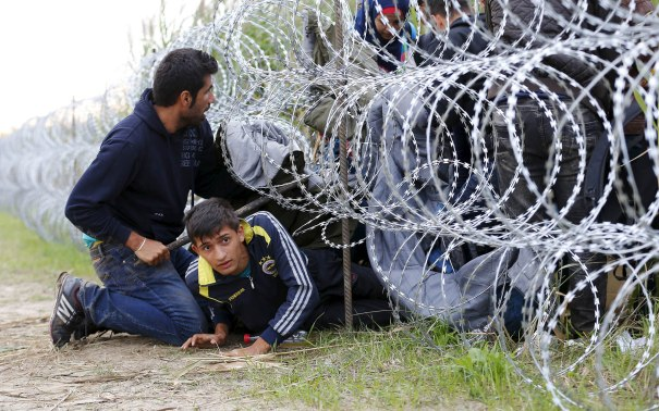 Syrian migrants cross under a fence into Hungary at the border with Serbia, near Roszke, August 26, 2015. Hungary's government has started to construct a 175-km-long (110-mile-long) fence on its border with Serbia in order to halt a massive flow of migrants who enter the EU via Hungary and head to western Europe. REUTERS/Laszlo Balogh